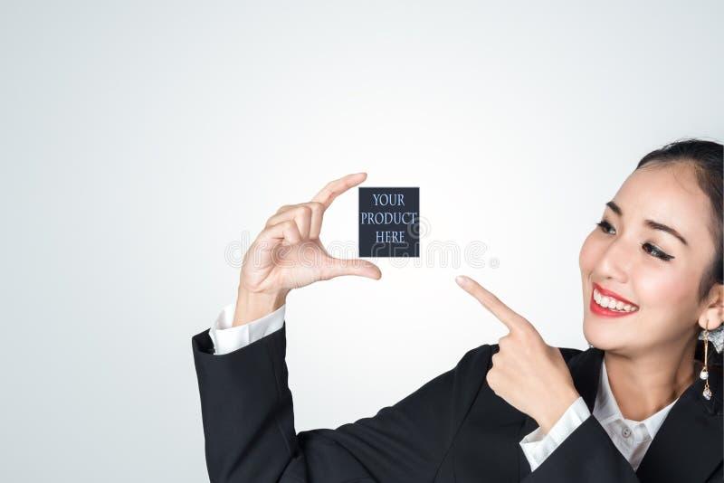 握空的手和指向您的产品地方的空的空间的女商人微笑这里为促进,产品 免版税库存图片