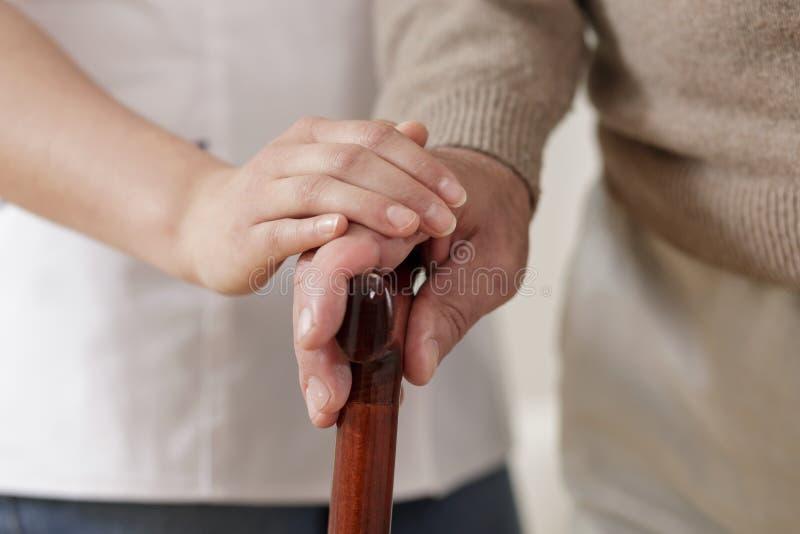 握老人手的护工 免版税库存照片