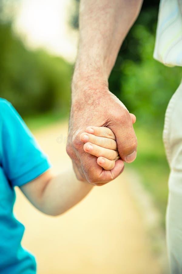 握老人的手的自然的孩子 图库摄影