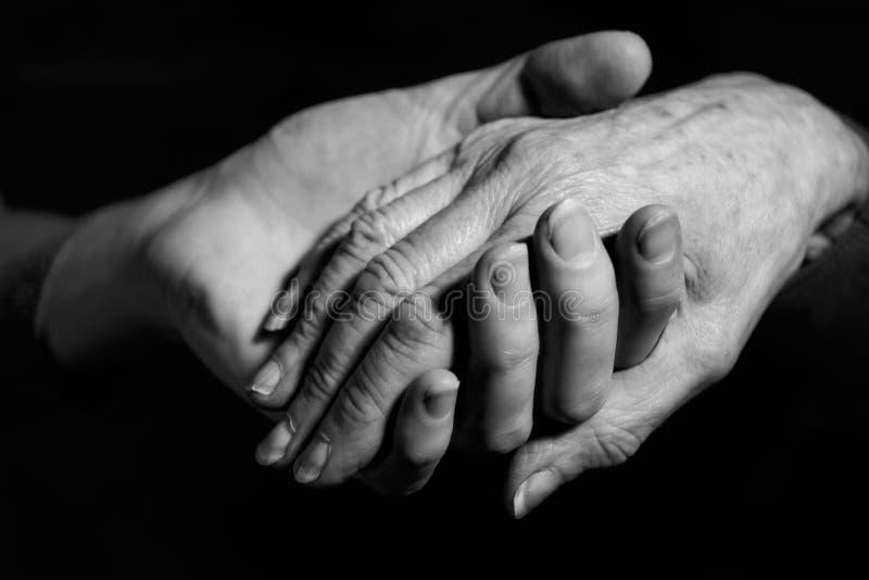 握老妇人的手的少妇单色射击 免版税库存图片