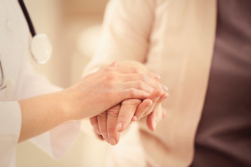 握老妇人的手的年轻医生, 免版税库存图片
