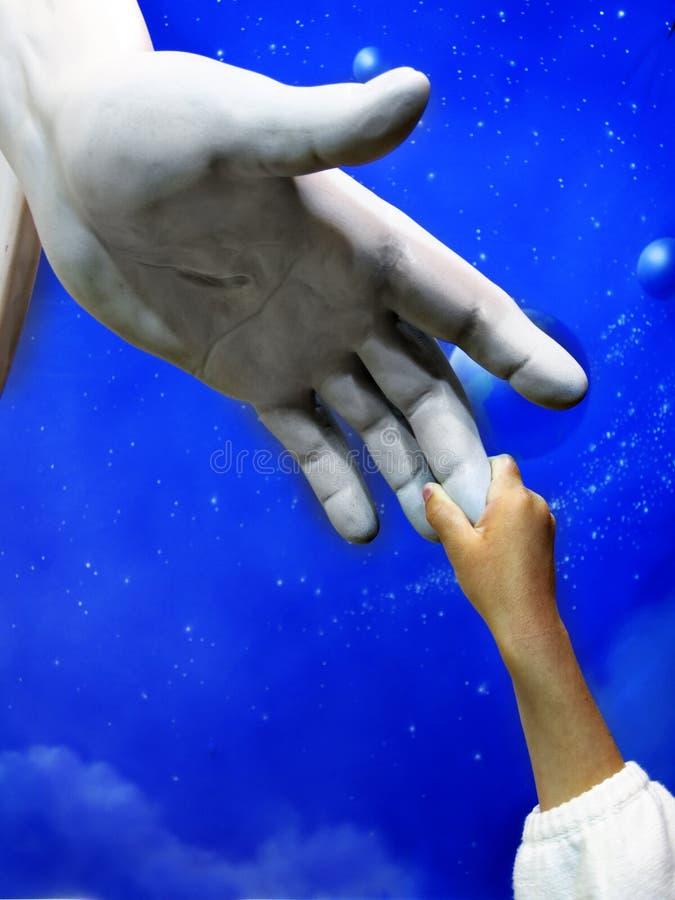 握耶稣雕象的手的孩子 免版税库存图片