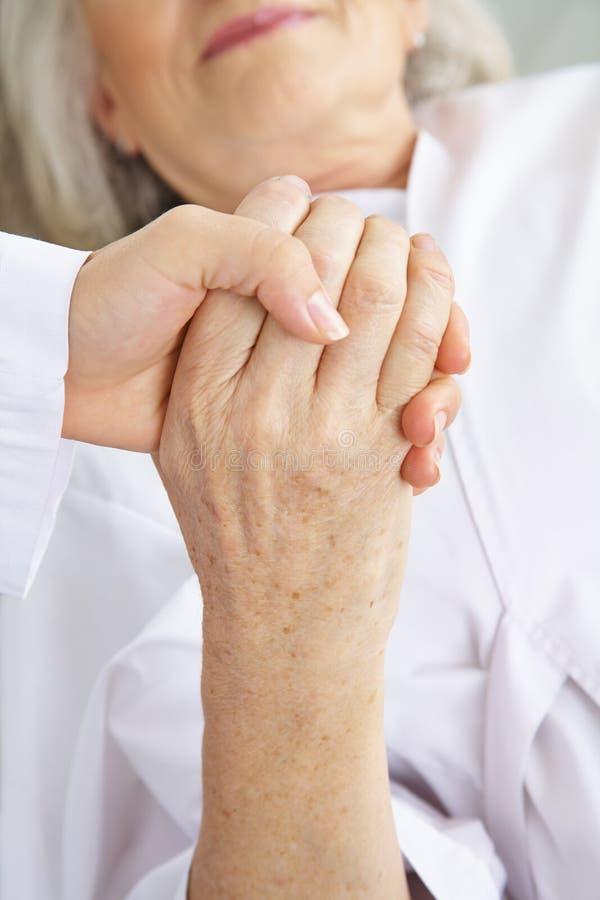 握资深患者的手的医生 免版税图库摄影
