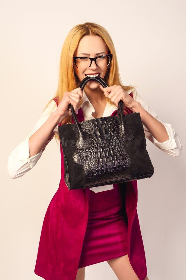 握黑皮包牙的年轻时兴的性感的俏丽的妇女 免版税图库摄影