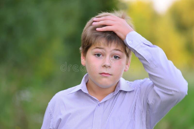 握他的在头后的吃惊的男孩手 免版税库存图片
