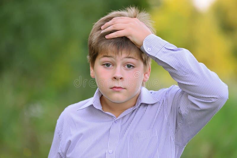握他的在头后的吃惊的男孩手 免版税库存照片