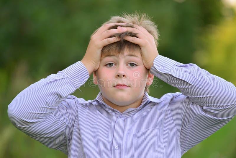 握他的在头后的吃惊的男孩手 库存照片