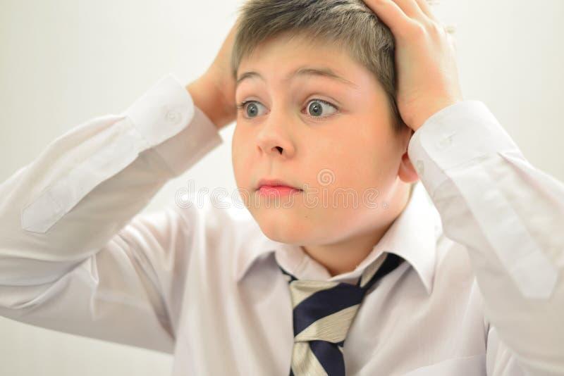 握他的在他的头后的吃惊的男孩手 免版税图库摄影