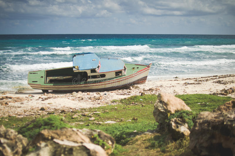 搁浅小船在多岩石的海滩, Isla Mujeres,墨西哥 免版税图库摄影