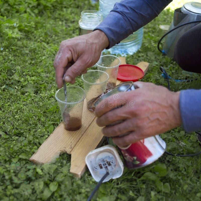 搅动在塑料杯子的手糖用咖啡 库存照片