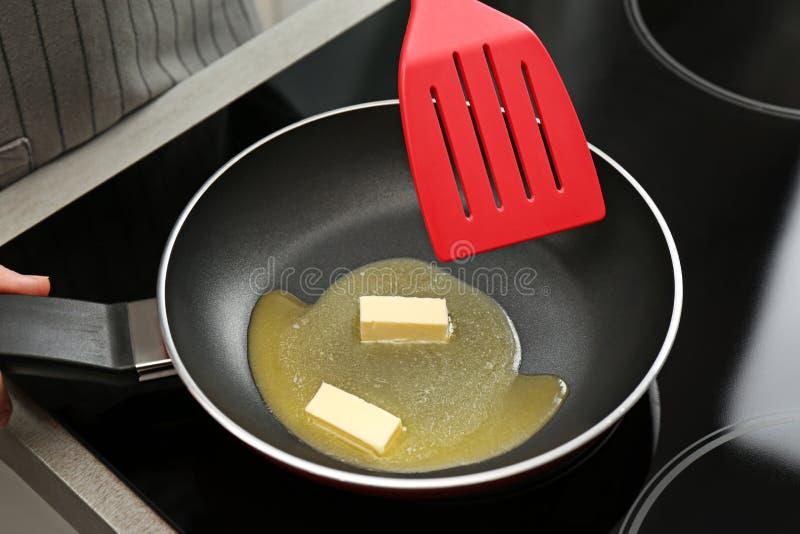 搅动在煎锅的妇女熔化黄油在火炉 免版税库存图片
