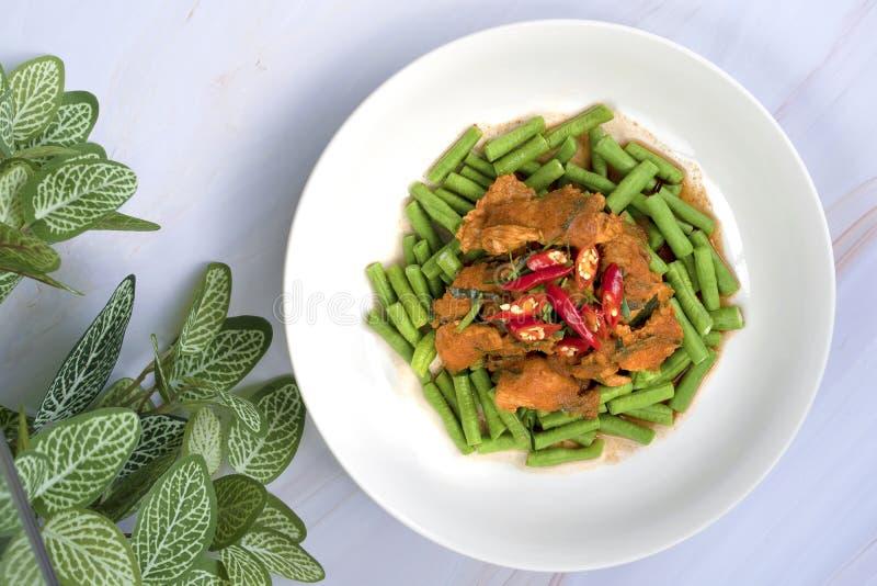 搅动在白色陶瓷板材的油煎的辣椒豆在白色大理石ta 免版税库存图片