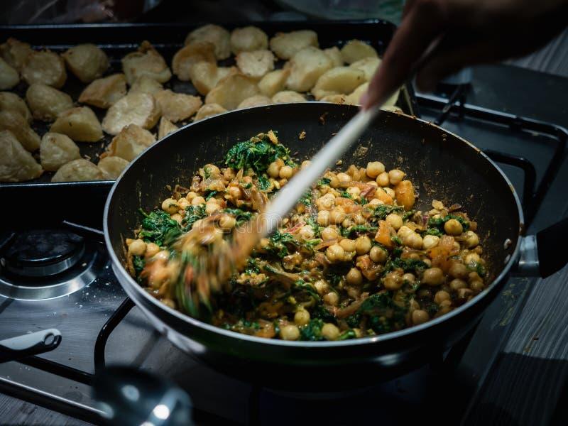 搅动在铁锅的手印度鸡豆和菠菜咖喱在煤气炉户内 图库摄影