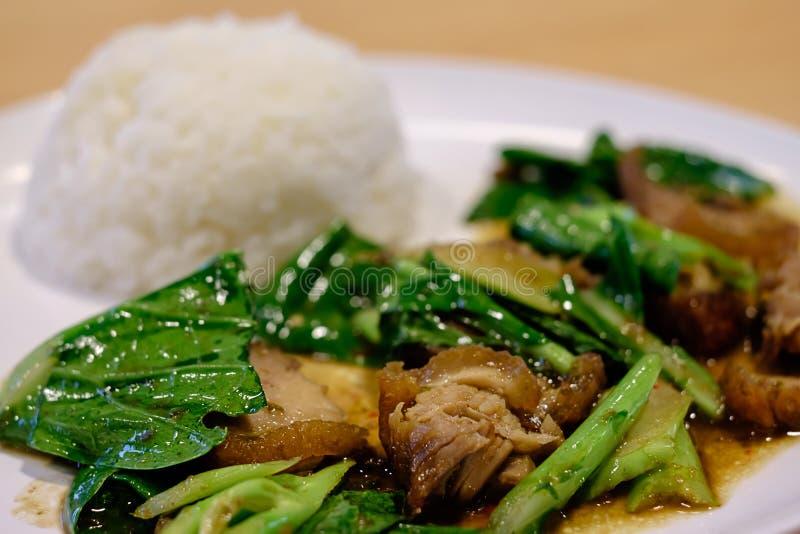 搅动油煎的无头甘蓝用酥脆猪肉和蒸的米 库存图片