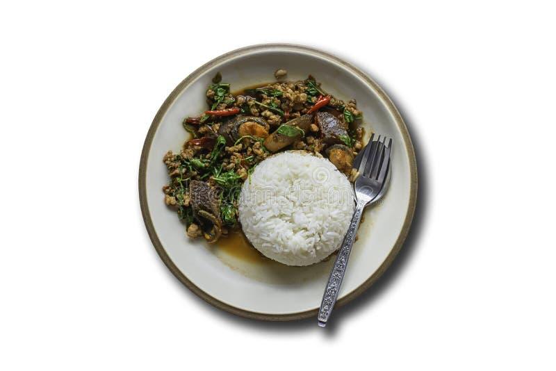 搅动油煎的蓬蒿叶子猪肉用米并且把被保存的鸡蛋放在与裁减路线的白色背景上 免版税库存照片