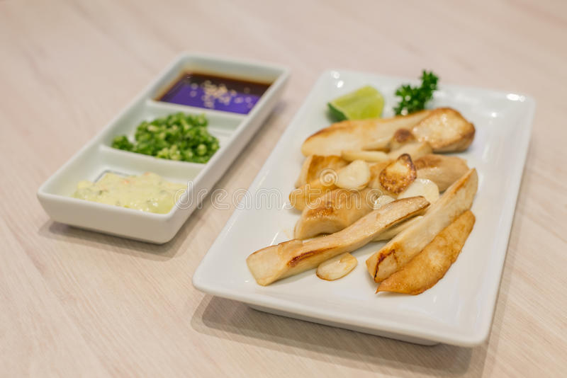 搅动油煎的eringii蘑菇和大蒜在白色板材 库存照片