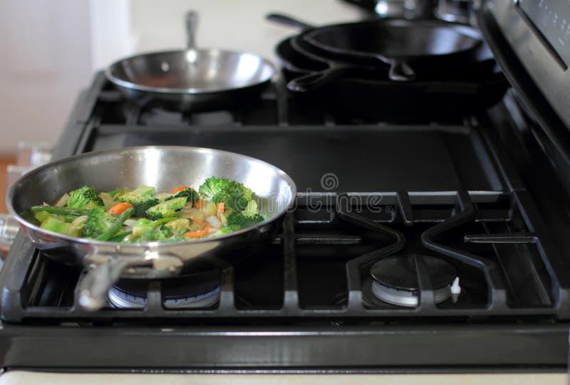 搅动烹调在一个不锈钢平底锅的油炸物菜 免版税库存照片