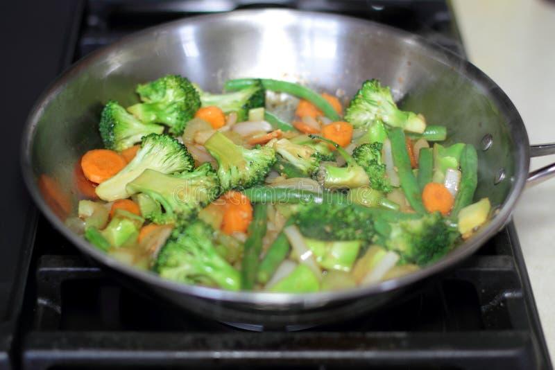 搅动烹调在一个不锈钢平底锅的油炸物菜 库存照片