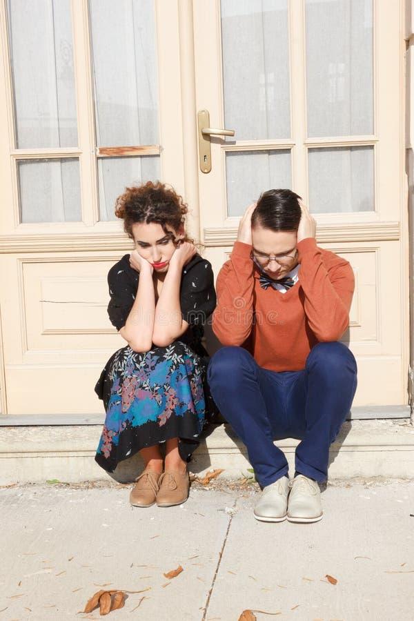 搅动的蹲下在房子前面的男人和妇女在stairw 免版税图库摄影