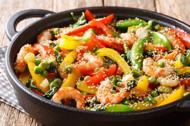 搅动虾油炸物用甜椒,葱,草本,荚,豌豆,在平底锅的芝麻特写镜头 ?? 图库摄影