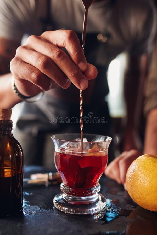 搅动negroni鸡尾酒的侍酒者手 免版税库存图片