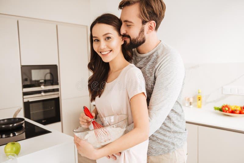 搅拌酥皮点心的微笑的年轻夫妇面团 免版税库存照片