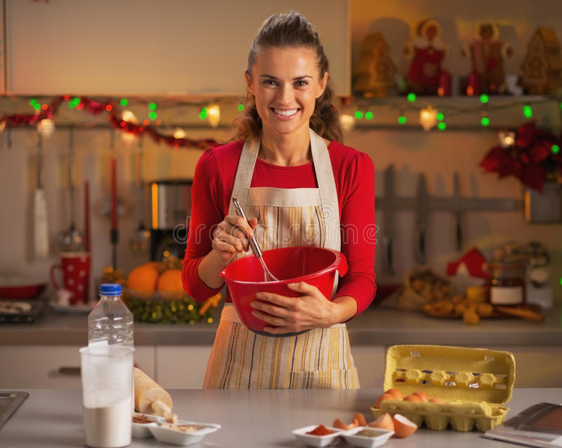 搅拌面团的愉快的年轻主妇在厨房里 免版税库存图片