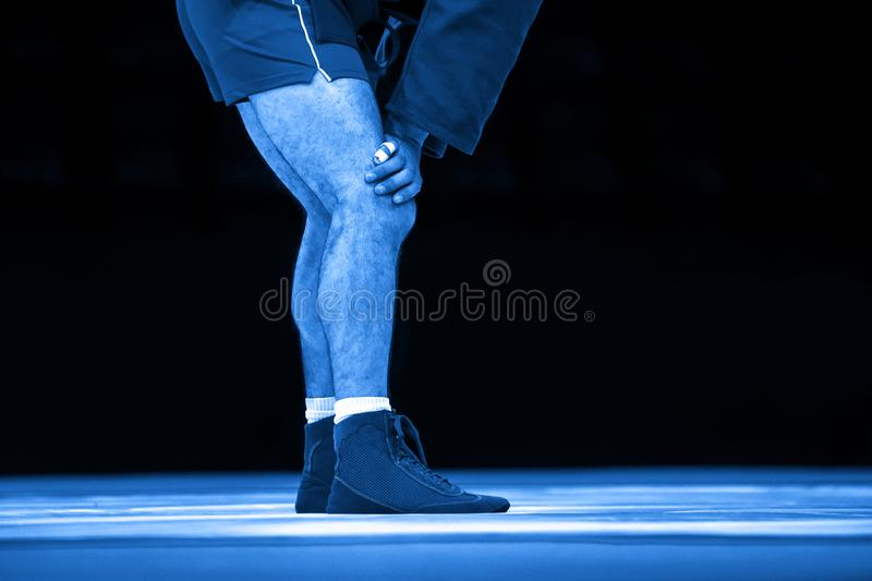搏斗在健身房的一张黄色搏斗的地毯的人 蓝色滤色器 库存图片