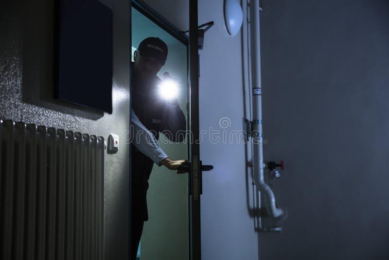 搜寻与手电的男性治安警卫 库存照片