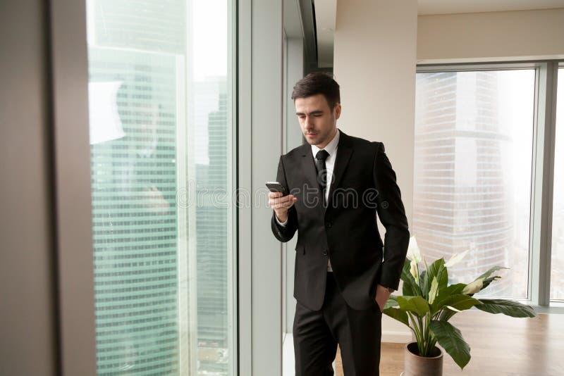 搜寻在智能手机的英俊的经理联络 免版税库存图片