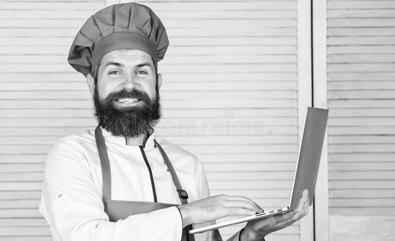 搜寻网上成份的人厨师烹调食物 在网上杂货店 : 在厨房的厨师膝上型计算机 库存图片