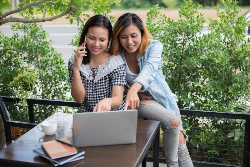 搜寻信息的两名年轻美丽的妇女在膝上型计算机comput 免版税库存照片