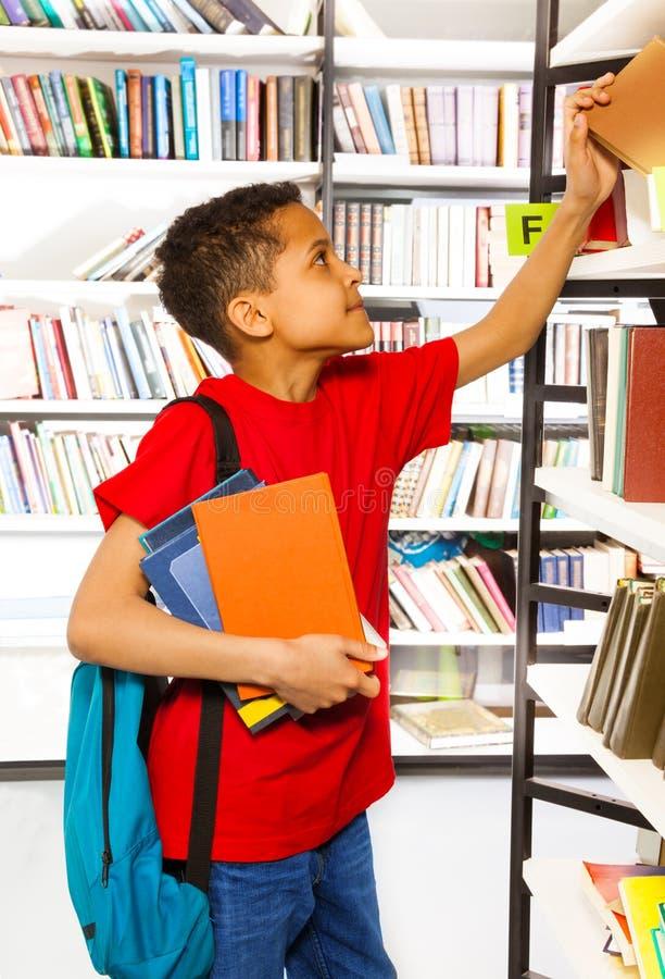 搜寻在图书馆书架的男孩书 免版税图库摄影