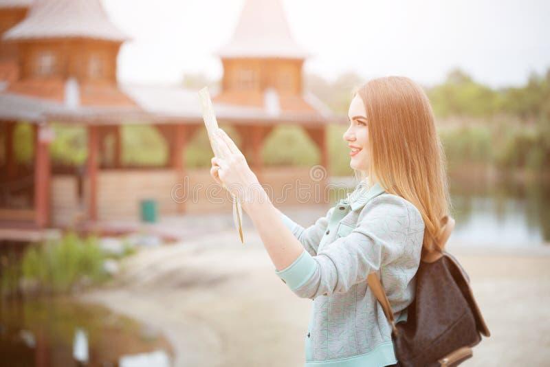 搜寻在地图,橙色日落光的旅客女孩的后部正确的方向,旅行沿欧洲 库存图片