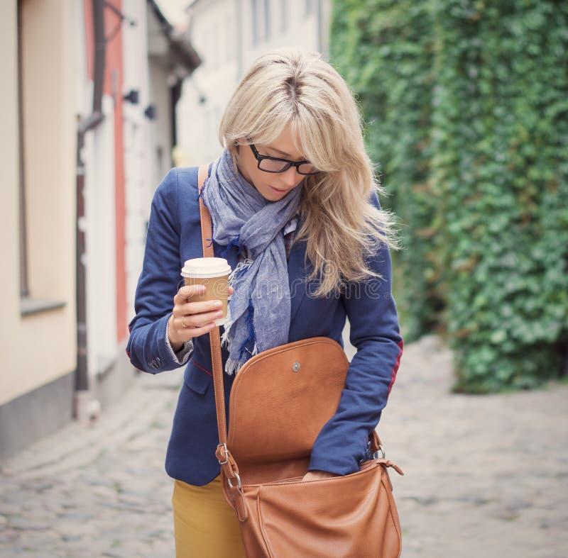 搜寻在她的提包的材料的妇女 库存照片