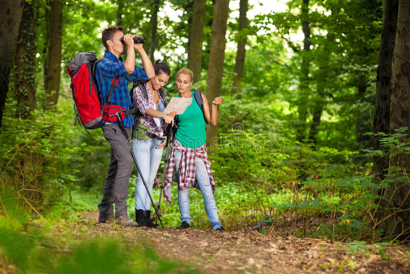 搜寻正确的方向的小组远足者 免版税库存图片