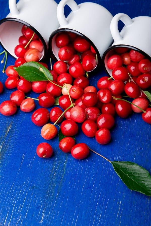 从搪瓷杯子的疏散樱桃 在铁杯子的樱桃在蓝色木背景 健康,夏天果子 樱桃 三 接近的u 库存图片