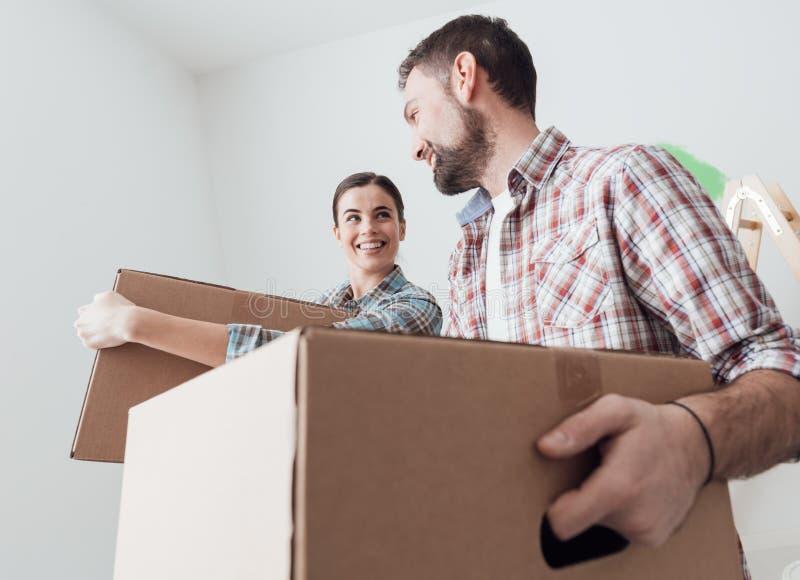 搬入一个新房的年轻夫妇 库存照片