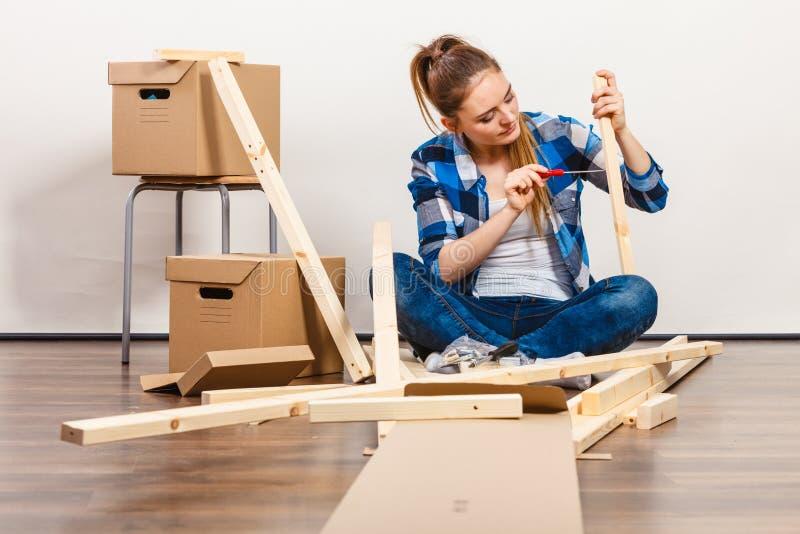 搬入公寓汇编家具的妇女 免版税图库摄影