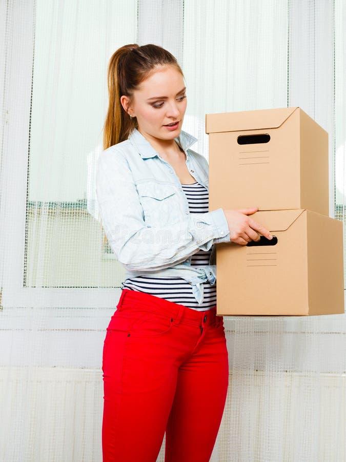 搬入公寓运载的箱子的妇女 库存照片