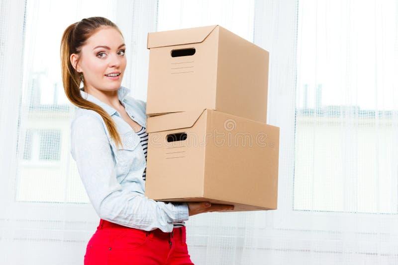 搬入公寓运载的箱子的妇女 免版税库存图片