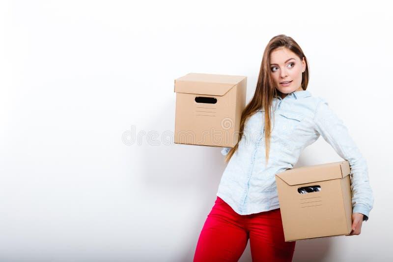 搬入房子运载的箱子的愉快的妇女 库存照片