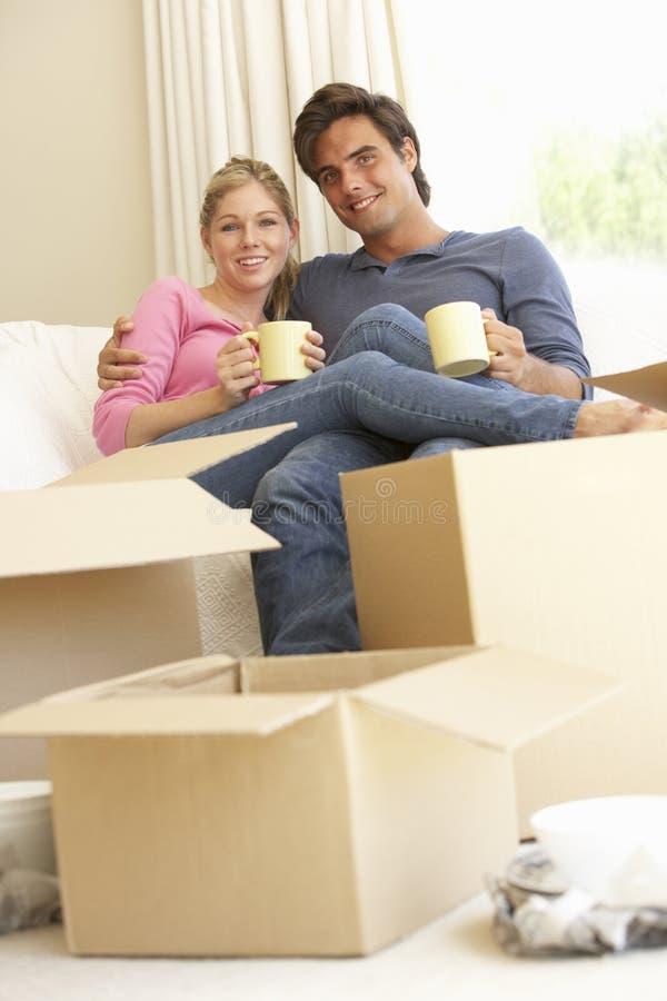 搬入新的家的年轻夫妇包围由包装盒 免版税库存图片