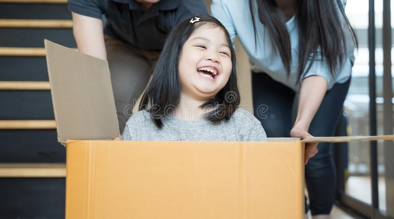 搬到有纸板箱的新房和演奏纸板箱的愉快的亚洲家庭画象  库存照片