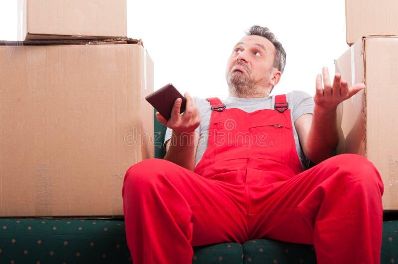 搬家工人人坐举行电话和打手势的长沙发 免版税图库摄影