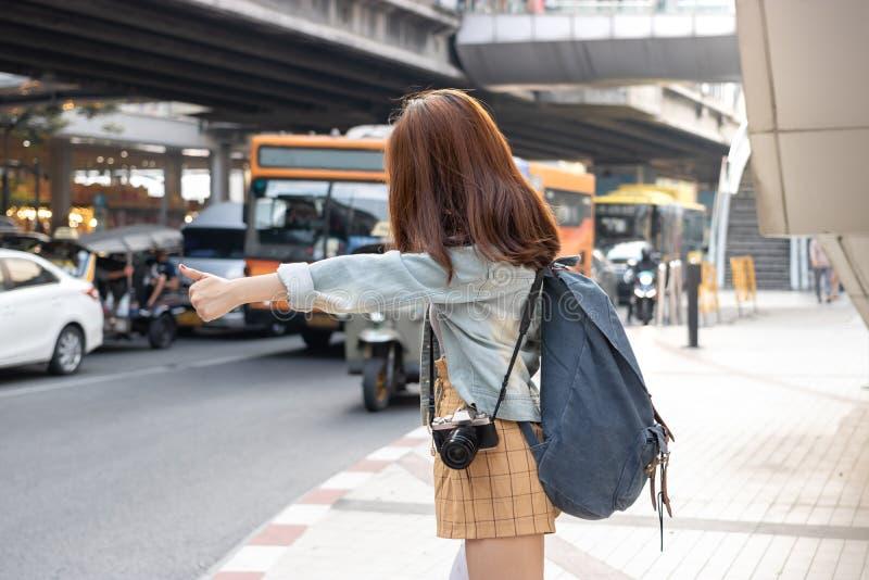 搭车在路的后面观点的年轻亚裔旅行女孩在城市 生活是旅途概念 免版税库存照片