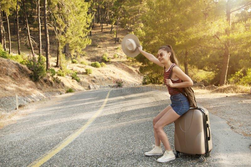 搭车旅游业概念 旅行走在路的旅行者妇女在假日旅行期间 免版税库存照片