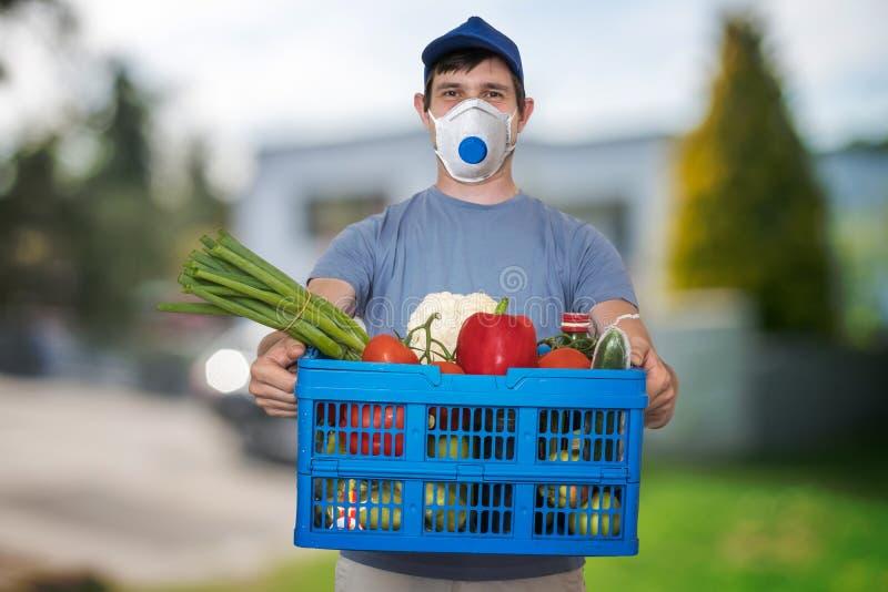 携带FFP3口罩的男子在病毒流行期间运送食物和食品 免版税库存图片