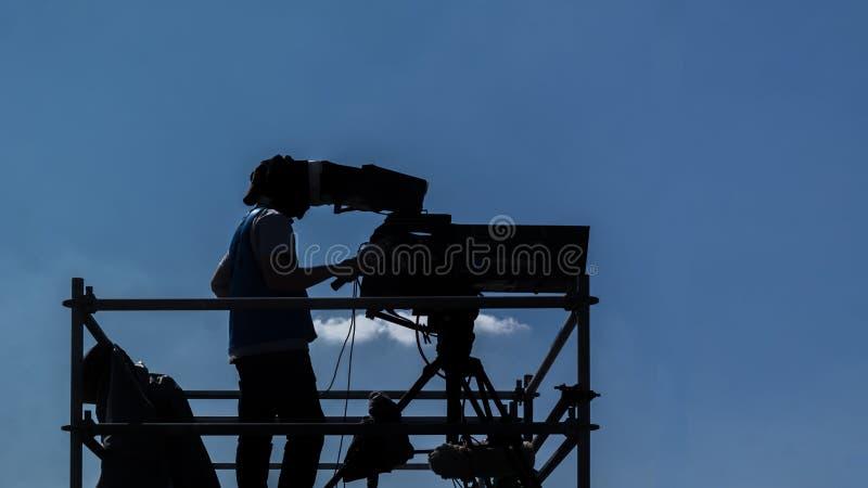 摄像头操作员-研究和摄制集合的人用他的设备 免版税库存图片