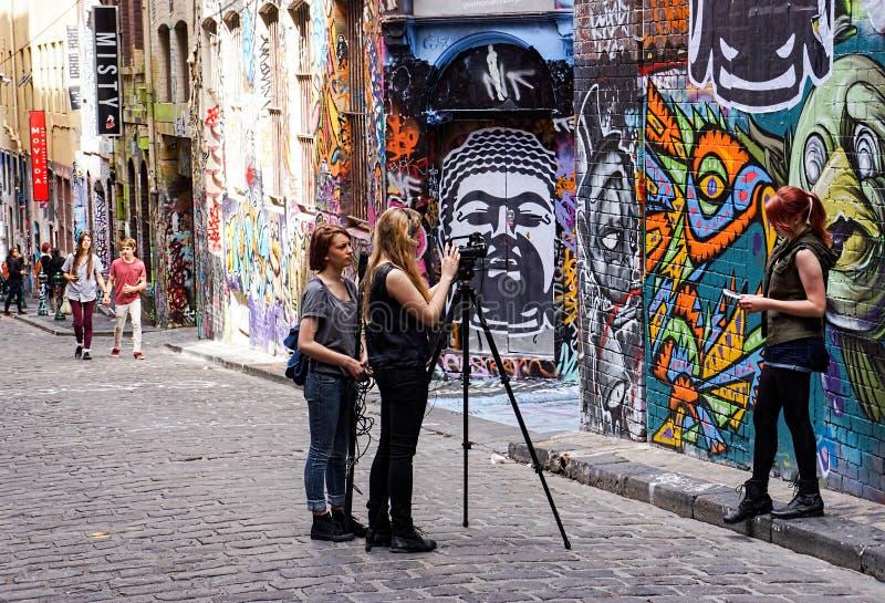 摄制在街道画艺术前面的学生采访 免版税图库摄影